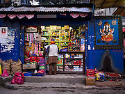 07 MARCH 2017 - KATHMANDU, NEPAL:  A shop that sells snacks and cigarettes near the Kamaladi Ganesh Temple, the most important Hindu temple dedicated to Ganesh, known as the overcomer of obstacles, in Kathmandu. The alcove on the right is used by sadhus who consult with people at the temple. In Hindu theology, Tuesdays are the best day to pray to Ganesh and the temple is very busy on Tuesdays. People frequently visit temples dedicated to Ganesh when they buy a new home or start a new job.    PHOTO BY JACK KURTZ