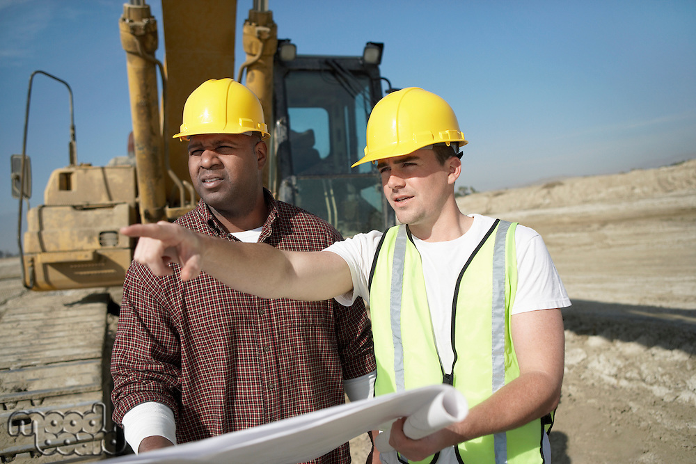 Construction Workers wearing hard hats standing in front of heavy equipment looking at plan