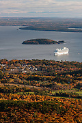 A cruise ship pulls into Frenchman Bay in a fall scene of Bar Harbor on Mount Desert Island, Maine, USA