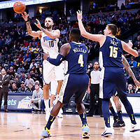 11 November 2017: Orlando Magic forward Evan Fournier (10) passes the ball past Denver Nuggets forward Paul Millsap (4) and Denver Nuggets center Nikola Jokic (15) during the Denver Nuggets 125-107 victory over the Orlando Magic, at the Pepsi Center, Denver, Colorado, USA.