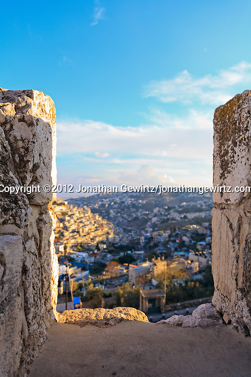 Closeup view of a battlement on the top of one of the exterior walls of the Old City of Jerusalem. The village of Silwan is visible through the gap in the wall.