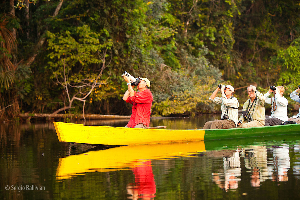 Tourists and guides travel via canoe along the edges of Chalalan Lodge lagoon in Madidi NP in Bolivia observing wildlife.