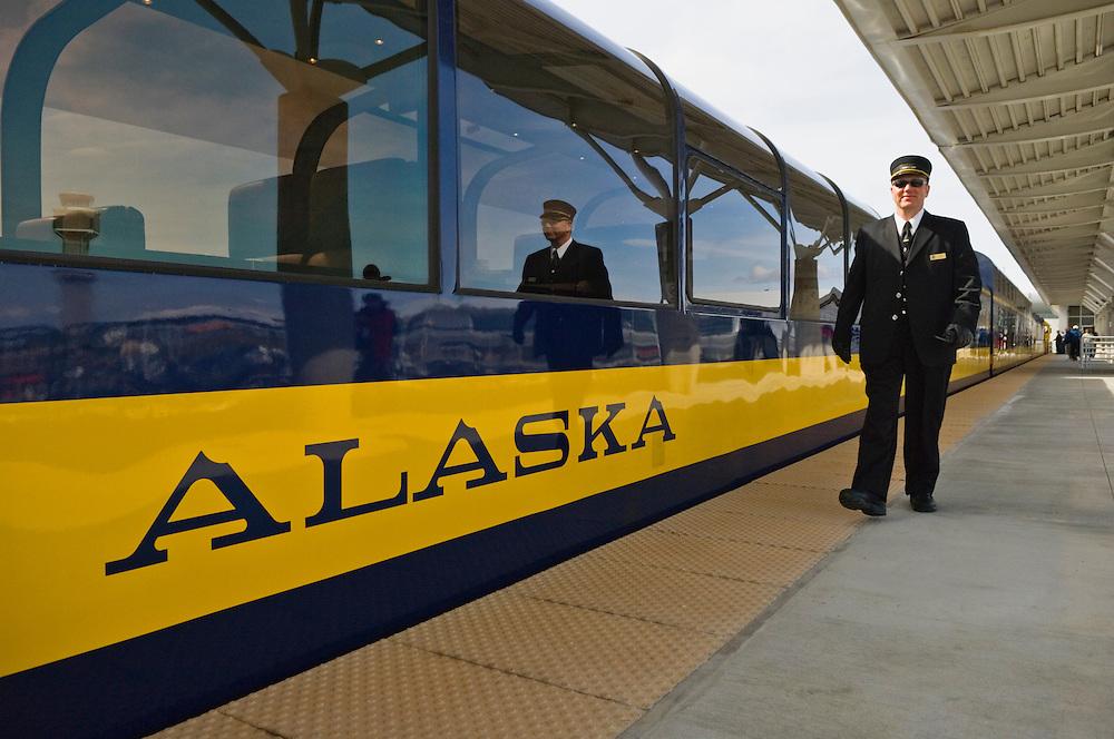 Alaska Railroad passenger car and conductor at Anchorage Airport train depot; Anchorage, Alaska.
