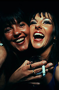 Two smiling female clubbers smoking, London, U.K, 1999.