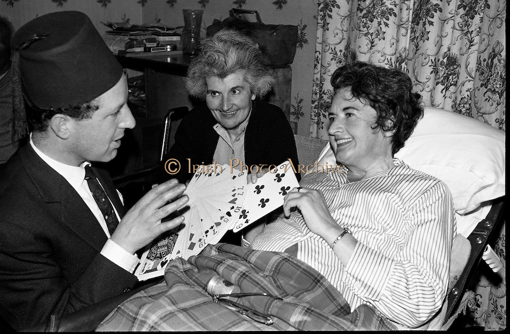 At the Cheshire Home, Shillelagh, Co. Wicklow, a variety concert featuring leading performers from Dublin was held for the entertainment of patients..Pick a card – any card! Magician Albert le Bas entertains a hospital patient..10.10.1963