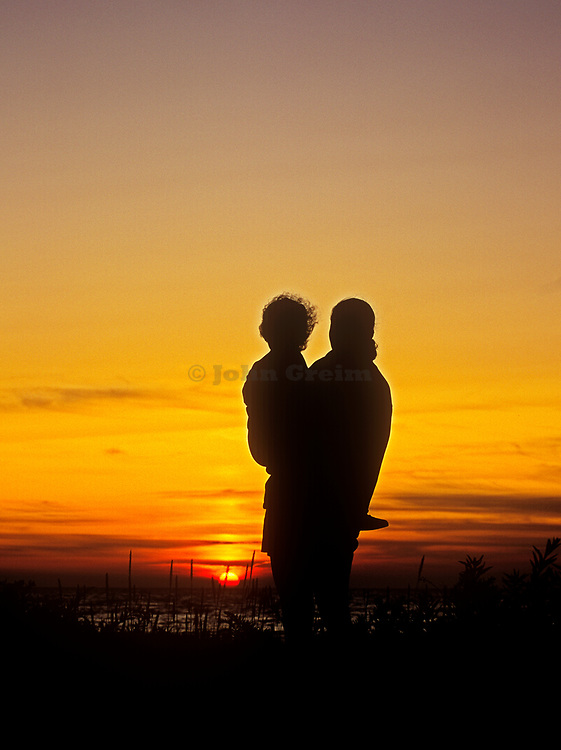 Silhouetted woman holding child while watching the sunset.