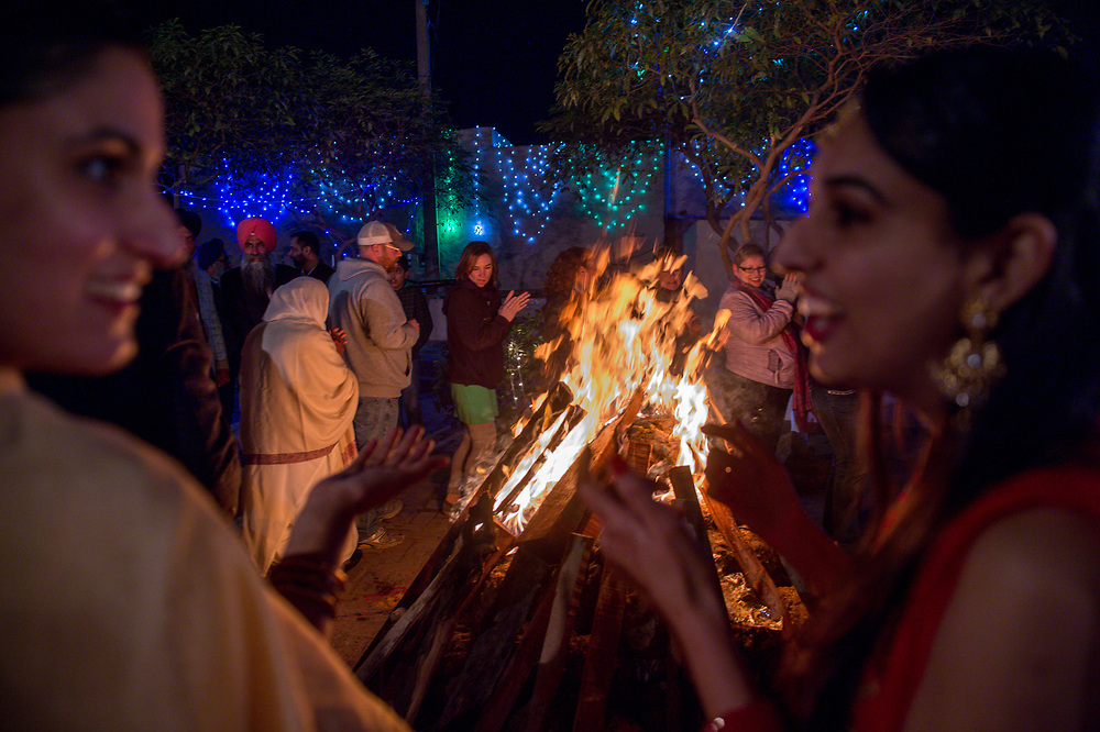 Women smiling and dancing as the Lohri bonfire burns in front of them in Punjab, India.