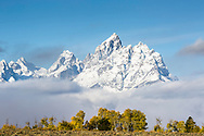 A bit of autumn and a bit of winter, a very grand Grand Teton rises above the valley of Jackson Hole in Grand Teton National Park<br />