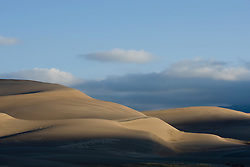 The dune field at sunrise.  Great Sand Dunes National Park and Preserve contains the tallest sand dunes in North America. The Dunefield, topping off with Star Dune at 750 feet, is created by sand trapped by the nearby Sangre de Christo Mountains (larger rougher grains and pebbles) and the San Juan Mountains (65 miles to the west).  Waterways such as Medano Creek help carry the sediment down to the San Luis valley where the dunes are found. Great Sand Dunes National Park and Preserve, Mosca, Colorado.