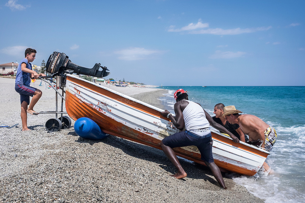 """Sheriffo, a refugee from Gambia is helping a group of local fishemen to keep the boat on shore. Sheriffo who got a house in Upper Riace was walking on the beach of Riace Marina trying to sell ethnic stuff to the few tourists """"there is no job here and the government subsidies is not enough for me and my wife. We found a good welcome but there is lack of employment for locals and for refugees. I'm trying to resist, I'm selling some stuff that my wife buy from an another seller but there is not tourism in this area, I don't know why."""" says Sheriffo, rescued by the Italian Coast Guard nine months ago and relocated in upper Riace with his wife. RIACE (ITALY) 03/08/16"""