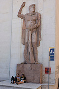 Young couple site beneath Fascist statue outside a government building in the northern Italian regional city of Trento.