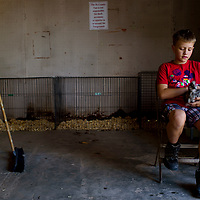 Garrett Balok sits with his silky chicken during check-in for the Bi-County Fair in Prewitt Thursday.