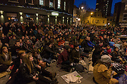 Accompanied by a pianist, south Londoners sit outside their rail station on whose wall is a screening of the silent film Easy Street starring a former local boy, Charlie Chaplin, kicking off a series of the Free Film Festival in Herne Hill in the London borough of Lambeth. There is no official record of his birth although Chaplin believed he was born atEast Street in nearbyWalworth. Chaplin's childhood was fraught with poverty and hardship, making his eventual trajectory 'the most dramatic of all the rags to riches stories ever told'. Easy Streetis a 1917 short comedy. In the film, the police are failing to maintain law and order and so it is Chaplin, as theLittle Trampcharacter, who steps forward (rather reluctantly) to rid the street of bullies, help the poor, save women from madmen and generally keep the peace.