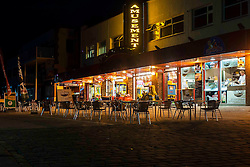Lights from the Amusement arcade and cafe with outside seating illuminate Coble Landing at the seaside holiday resort of  filey North Yorkshire<br />