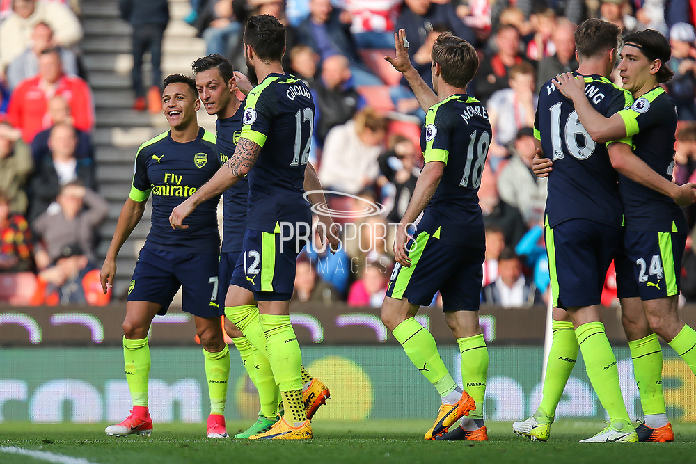Arsenal forward Alexis Sanchez leads the celebrations as Arsenal midfielder Mesut Ozil scores Arsenal's second goal (0-2) during the Premier League match between Stoke City and Arsenal at the Bet365 Stadium, Stoke-on-Trent, England on 13 May 2017. Photo by Aaron  Lupton.