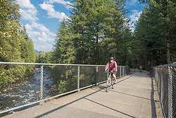 United States, Washington, man riding bicycle on bridge over Snoqualmie River, Snoqualmie Valley Recreation Trail
