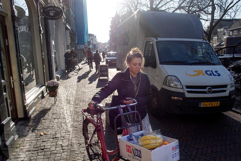 Een vrouw moet met haar fiets met boodschappen voorbij een vrachtwagen lopen die staat uit te laden op de Oudegracht in Utrecht.<br /> <br /> A woman has to walk with her bike with groceries to pass a truck which is blocking the Oudegracht in Utrecht.