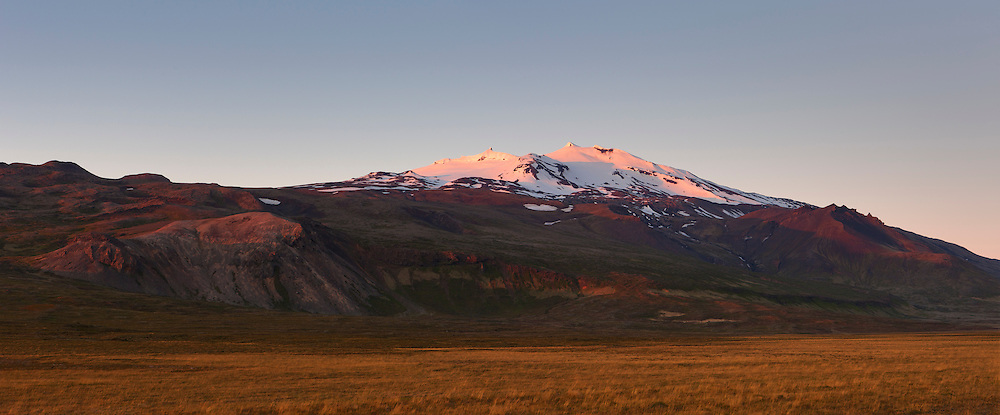 "The last light of day illuminates Snæfellsjökull, a 1,446 meter (4,744 foot) stratovolcano located in western Iceland. The volcano, which is active, last erupted approximately 1,800 years ago, creating lava fields at its base. The mountain is technically named Snæfell; Snæfellsjökull is the name of the glacier at its peak. It is commonly called Snæfellsjökull, however, to avoid confusing it with several other mountains with the same name. Snæfellsjökull means ""snow glacier mountain,"" and it was featured in the 1864 novel ""A Journey to the Center of the Earth"" by Jules Verne."