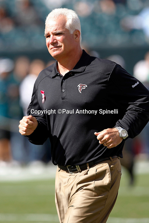 Atlanta Falcons Head Coach Mike Smith jogs off the field after pregame warmups during the NFL week 6 football game against the Philadelphia Eagles on Sunday, October 17, 2010 in Philadelphia, Pennsylvania. The Eagles won the game 31-17. (©Paul Anthony Spinelli)