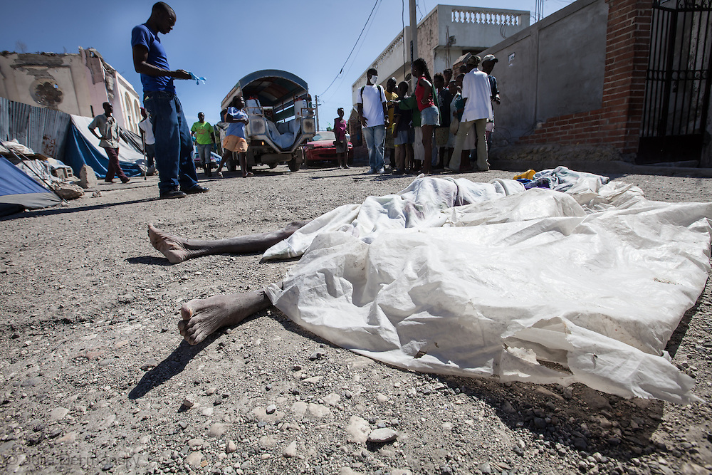 Minister of Health workers prepare Charite Charle's body, a cholera victim,  found next the the National Cathedral where she lived on the streets with her two children, before taking it away . The Cholera epidemic that started in the north spread to Port-au-Prince.