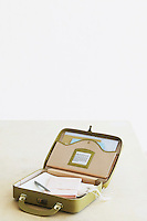 Suitcase with stationery items elevated view studio shot