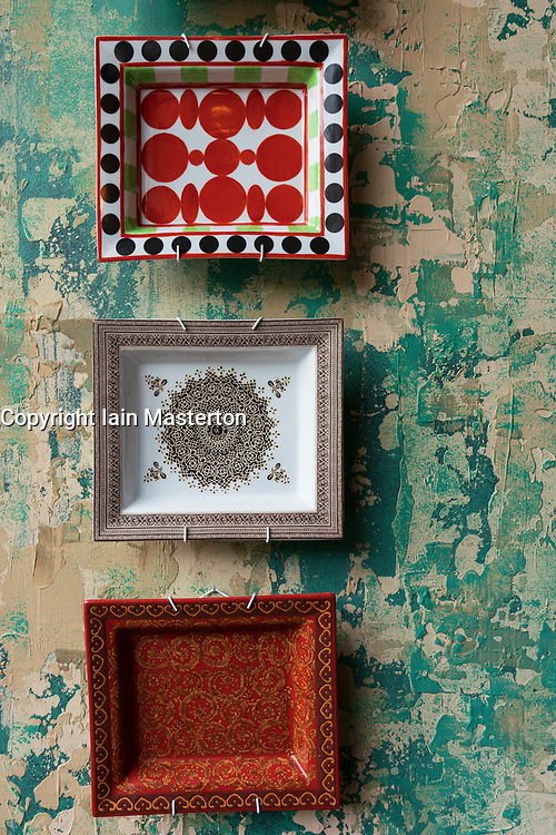 Detail of ceramic plates with Middle Eastern design on wall with peeling paint.