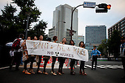"""TOKYO, JAPAN, 28 SEPTEMBER - Kasumigaseki - The woman's active group """"KNOW NEW KISS"""" (Japanese phonetically : No Nukes) at the anti-nuclear demostration in front of  the National Diet Bulding (Kokkai Gijidou) - Following shyly the example of the Femen's Ukrainian activist, they use the charm of their  naked shoulder an belly to protest about  the resuption of the nuclear power after Fukushima's crisis. - September 2012"""