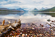Driftwood accents the already rich texture of the rocky shore of the reflective Lake McDonald in Glacier National Park.