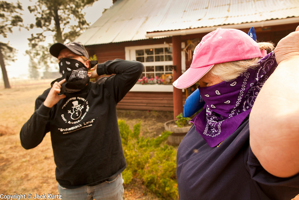 "05 JUNE 2011 - GREER, AZ:  Kristi Spillman (CQ LEFT) and Judy Cline (CQ) talk and put on bandanas before leaving their businesses in Greer Sunday. Spillman operates the Frosty Bottom Cafe and Cline the ""Quacker Barrel"" (CQ QUACKER) The fire grew to more than 180,000 acres by Sunday with zero containment. A ""Type I"" incident command team has taken command of the fire.  PHOTO BY JACK KURTZ"