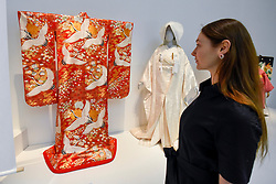 "© Licensed to London News Pictures. 26/02/2020. LONDON, UK. A staff member views works on display. Preview of ""Kimono: Kyoto to Catwalk"", an exhibition celebrating the Japanese kimono.  Artworks are on show at yje V&A museum in South Kensington 29 February to 21 June 2020.  photo credit: Stephen Chung/LNP"