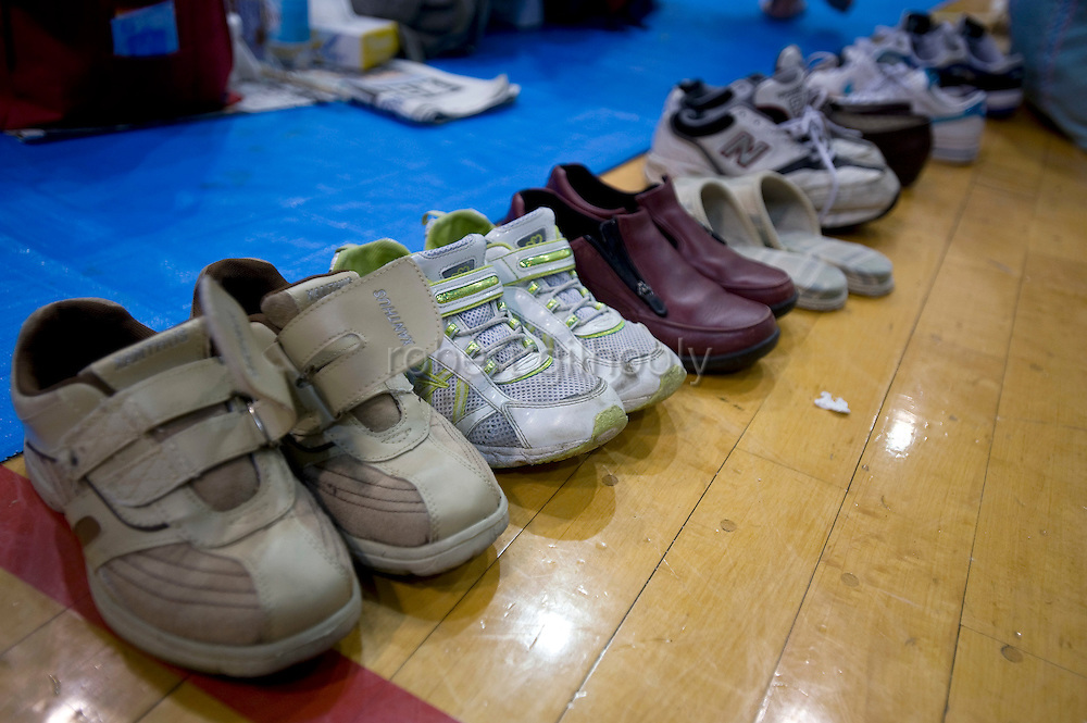 Shoes are lined up at the entrance to a refuge shelter in Iwaki City, northeastern Japan on 12 March, 2011. Around 300 people, many affected by an explosion at a nearby nuclear plant, others by Japan's biggest ever temblor on 12 March, took shelter at the ad hoc shelter set up inside a local gymnasium about 30 km from the nuclear accident.  Photographer: Robert Gilhooly