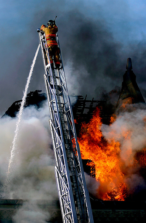 Lt. Todd Foster battles a fire from the top of a ladder truck at Eastern Illinois University's Blair Hall Wednesday, April 28, 2004, in Charleston, Ill. No one was injured in the blaze, which was confined to the top floor of Blair Hall, a three-story limestone building, spokeswoman Vicki Woodard said. The building houses the university's graduate school and a number of other departments, including sociology-anthropology, minority affairs, African-American studies and international affairs.