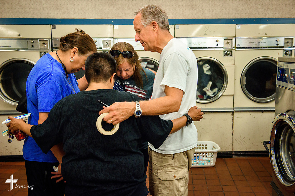 "The Rev. Charles ""Carlos"" Boerger, pastor of St. Paul Lutheran Church, San Antonio, Texas, prays with (left to right) Maria Perez, Helen Borrego, and Emma Perez at Laundry Love on Wednesday, Aug. 2, 2017, at the E-Z Wash laundromat in San Antonio. The monthly ministry event is supported by a grant through the ""Stand With Your Community"" program, which was made possible by a partnership between the LCMS, Thrivent Financial and Lutheran Church Extension Fund. LCMS Communications/Erik M. Lunsford"