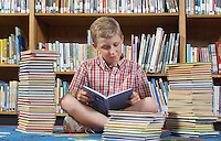 Boy sitting on the floor and reading book in library