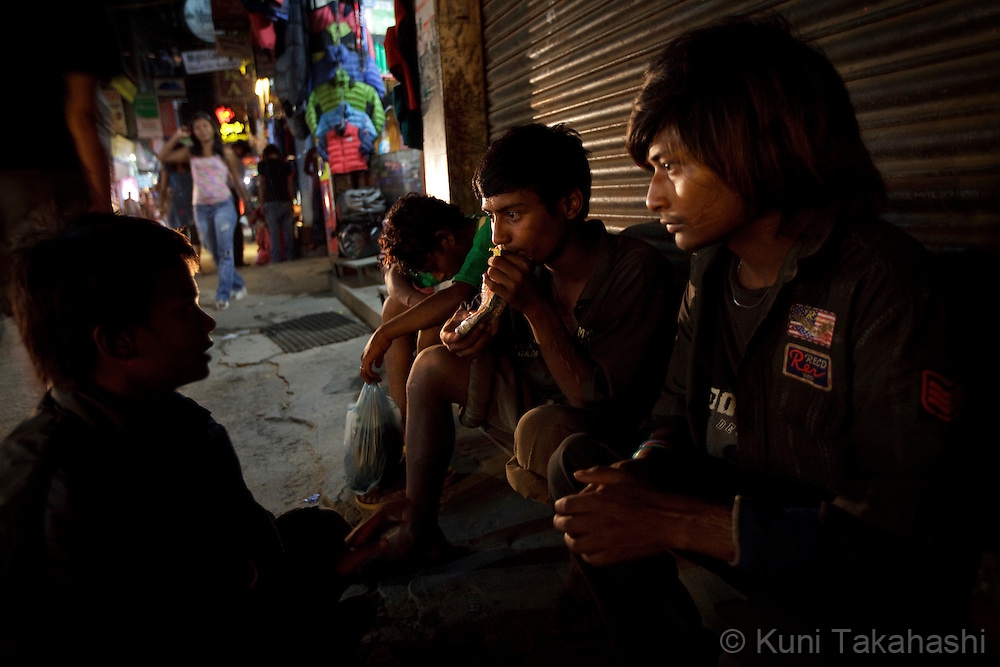 Krishna, center, hangs out with other street children and sniffs glue to get high at commercial area in Kathmandu, Nepal on Aug 17, 2012..There are estimated around 5,000 street children working and living on the streets of Nepal and the number continues to grow with roughly 300 to 500 children leaving home every year. Some do so because of abusive, alcoholic parents, maltreatment at home, and the temptation to earn more money. They often end up taking drugs, abusing alcohol, and even suffering sexual abuse by locals and foreign tourists..(Photo by Kuni Takahashi)