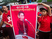 09 NOVEMBER 2015 - YANGON, MYANMAR:  Teenagers hold up a poster of Aung San Suu Kyi at NLD headquaters Monday. Thousands of National League for Democracy (NLD) supporters gathered at NLD headquarters on Shwegondaing Road in central Yangon to celebrate their apparent landslide victory in Myanmar's national elections that took place Sunday. The announcement of official results was delayed repeatedly Monday, but early reports are that the NLD did very well against the incumbent USDP.    PHOTO BY JACK KURTZ