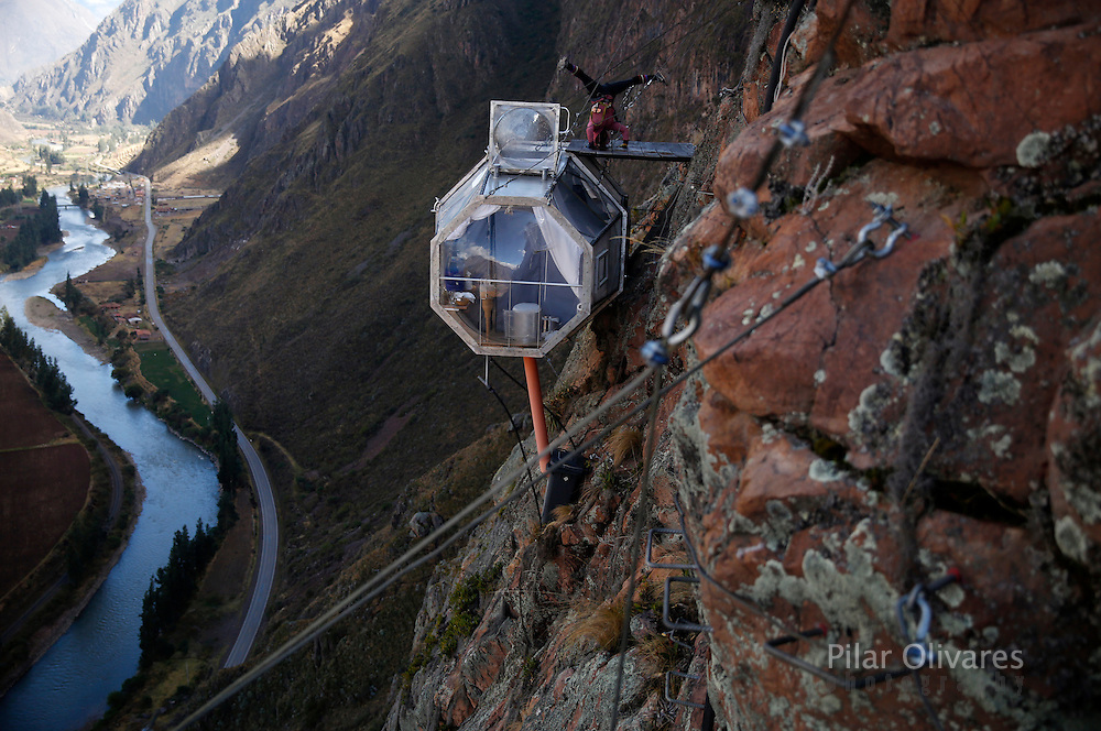 "A guest performs yoga above the sleeping pod at the Skylodge Adventure Suites in the Sacred Valley in Cuzco, Peru, August 14, 2015. Tourists taking on an arduous climb up the steep cliff face of Peru's Sacred Valley are being rewarded for their efforts by being able to spend the night in transparent mountaintop sleeping pods at the ""Skylodge Adventure Suites"". To reach the pods, visitors need to climb 400 metres of via ferrata (a steel cable and rungs) up the valley side or hike an intrepid trail through zip lines. REUTERS/Pilar Olivares"