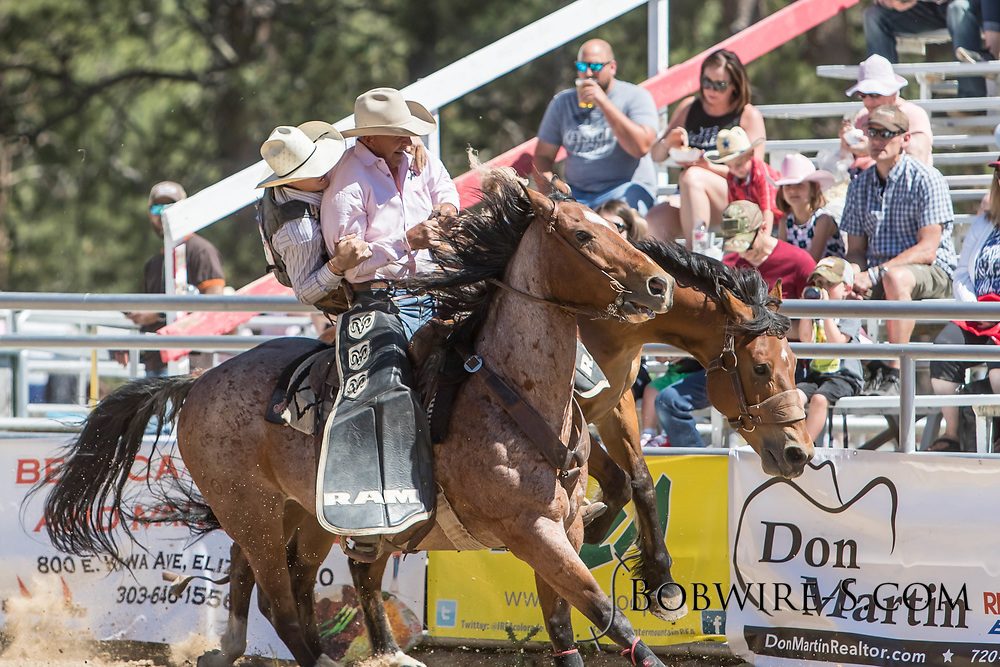 Pickup man Scott McClain helps Saddle bronc rider Mason Mardesich off of Summit Pro Rodeo's 011 Wrong Number in the first performance of the Elizabeth Stampede on Saturday, June 2, 2018.