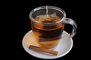 A cup of hot black tea with cinamon On black Background