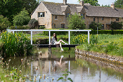 © Licensed to London News Pictures. 25/05/2017. The Slaughters, Cotswolds, UK. Pictured, HEIDI PERKINS from Sydney, Australia on holiday visiting her father, a London taxi cab driver. HEIDI is pictured sitting on the walking bridge in the centre of the Slaughters, a well known tourist spot in the Cotswolds. Photo credit: Dave Warren/LNP