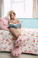 Young girl (5-6) sitting on bed wearing bunny costume and monster slippers reading book