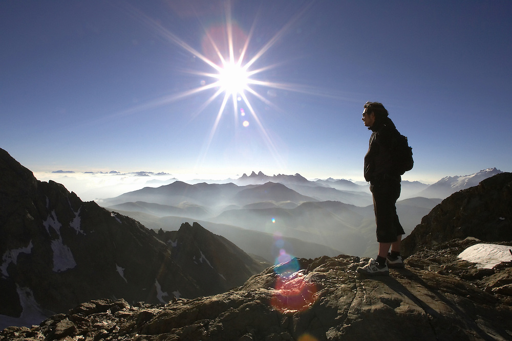 Lifestyle. A Man stands on a mountain peak, taking in the majesty of the mountains