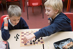 Two primary school children playing a game of chess in an after school club,