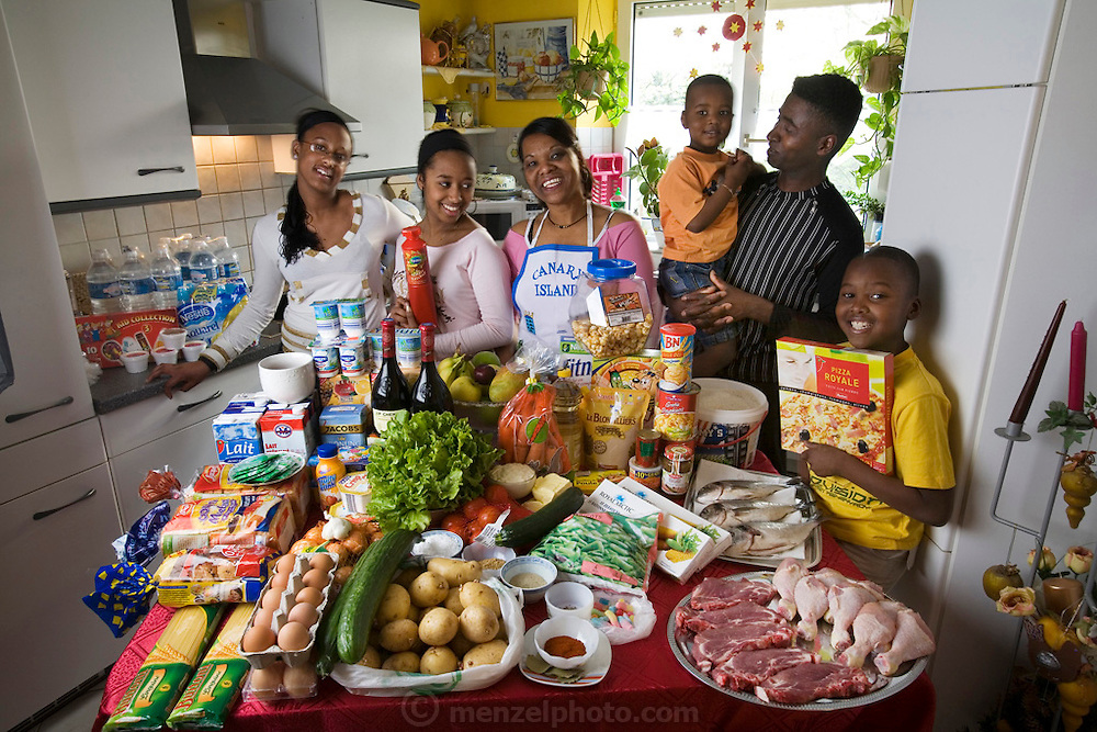 The Lopes-Furtado family from Cabo Verde in the kitchen of their home in Luxembourg with one week's worth of food. Natercia Lopes-Furtado and her husband Ernesto Lopes Sanchez, 47, with their children: Darlene, 16, Melody, 14, Teddy, 9, and Lionel, 4. Cooking method: electric stove, oven and microwave. Food preservation: electric refrigerator and freezer. Model Released.