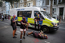 © Licensed to London News Pictures. 25/08/2019. London, UK. Police watch over as revellers enjoy J'ouvert, a paint fight that officially marks the start of the Notting Hill carnival. The two day event is the second largest street festival in the world after the Rio Carnival in Brazil, attracting over 1 million people to the streets of West London. Photo credit: Ben Cawthra/LNP