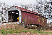 "McAllister Covered Bridge (126 feet long), built in 1914 by J.A. Britton over Little Raccoon Creek, on County Road 400S, Parke County, Indiana, USA. Red and white paint protects the wood. The ""Cross this bridge at a walk"" sign requires slow vehicle speed."