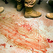 Canadian medics at a Canadian Forward Operating Base are seen standing on a blood stained floor while treating four Afghan civilians one of which later died from his wounds after they suffered injuries from an apparent improvised Explosive Device (IED) in Zhari District Afghanistan. Zhari and the adjacent Panjwai District have been the most volatile area of Afghanistan over the past two years and the site of NATO's largest ever land battle. Soldiers felt that the civilians injuries seemed more associated with an accident from setting an IED than stumbling across one.<br /> &copy; Louie Palu/ZUMA Press/New America Foundation