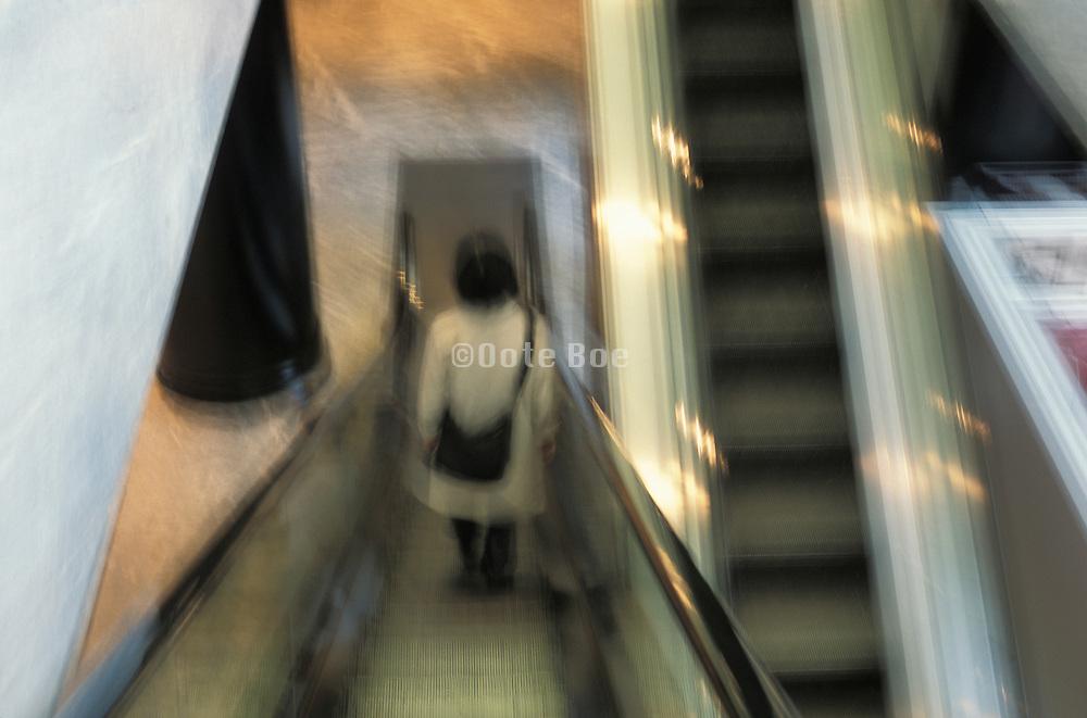 Person ascending an escalator
