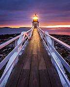 The Marshall Point Lighthouse in Port Clyde, Maine, sits on one of the most beautiful ocean outlooks in the state.  Every time I visit, I'm blown away by the scenery and inspirational quality of this iconic location.  This lighthouse achieved nationwide attention in the movie &quot;Forrest Gump&quot;, when the main character runs to the 'end of the road', which is portrayed as this exact spot.  Pretty neat.<br /> <br /> This particular evening was one of the most spectacular light shows I've seen.  This is the tail end of the light of day, as you can see there was a small window of light on the horizon, and the light from the beacon was starting to cast its own glow on the scene.