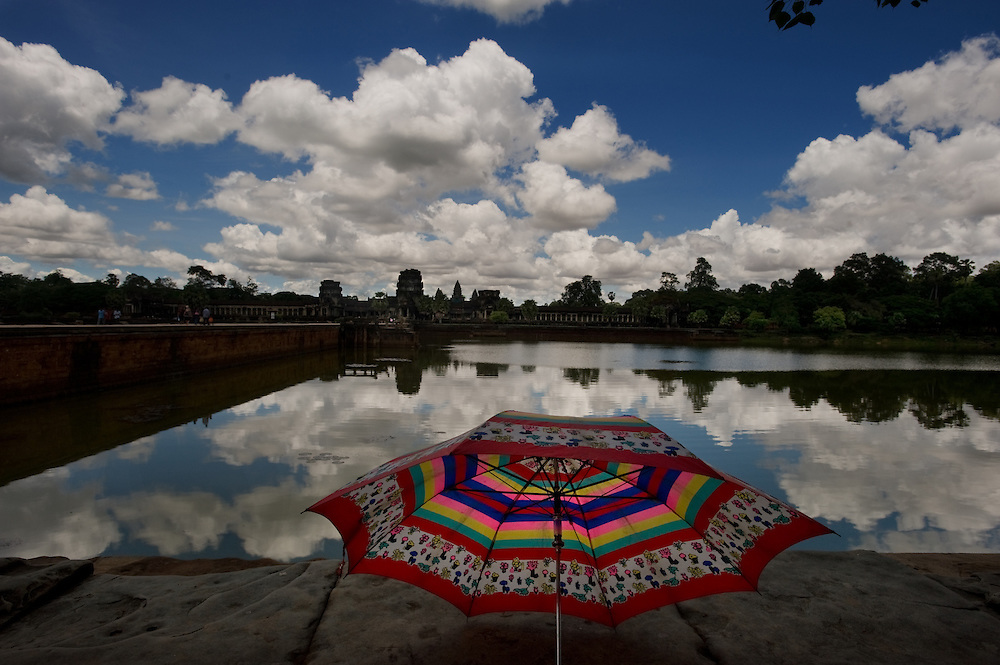 An umbrella its on the wall with a view of the moat surrounding Angkor Wat in the distance.